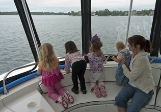 """From left, Meagan Boone, 4; Ava Szakaly, 3; Samantha Hays, 3; McKanna Hays, 10 months; and Karyn Hays look out for Normie on the first of many planned summer """"Lake Norman Monster Cruises."""" On the cruises, families watch not only for Normie the Lake Norman Monster but learn about conservation and the lake-area environment. Photos by Jeff Willhelm"""